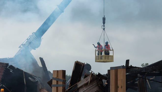 An AFT investigator and a local contractor hang from a basket to get a better vantage point of the burned out structure, Tuesday, August 8, 2017, while a specialized fire investigation team from the ATF help investigate the Windsor Mill fire that occurred just before 2 a.m. Sunday morning.