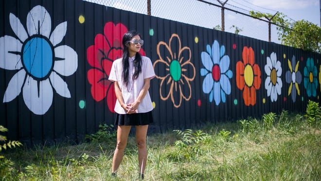 "Local muralist Louise ""Ouizi"" Jones, 29, with her recent piece, ""Daisy Chain"" located along the southbound service drive wall of I-75 in Detroit on Tuesday, August 8, 2017. The piece is part of a new program hiring local street artists to create murals in high visibility locations across the city of Detroit. (Brittany Greeson, Special to the Free Press)"