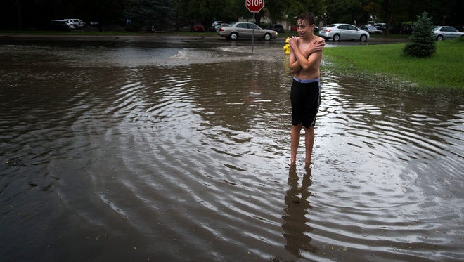 Xander Morgon, 14, gets a little cold while standing in the flooded out street corner of South Lemay Avenue and East Lake Place, Thursday, August 10, 2017 in Fort Collins, Colo.