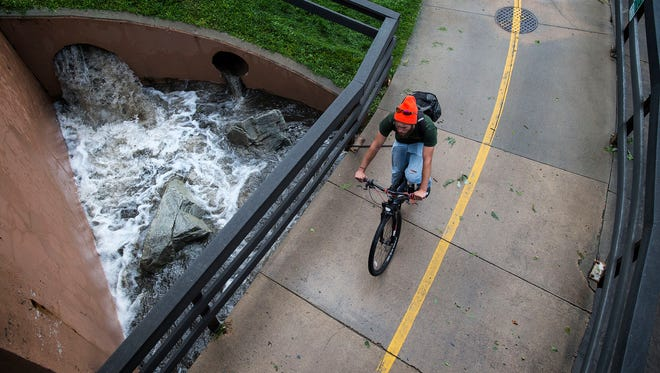 A cyclist heads to the underpass running under South College Avenue at Creekside Park while storm water bursts from a storm drain, nearly reaching the walkway, Thursday, August 10, 2017 in Fort Collins, Colo.