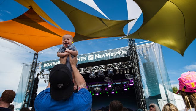 Brian Edman hoists up seven-month-old Harvey Edman while Write Minded plays the Mountain Avenue stage, Saturday, August 12, 2017 at the Bohemian Nights at NewWestFest music festival in Downtown First Collins, Colo.