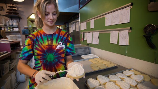 Emily Reynolds frosts a fresh batch of cookies, Saturday, August 12, 2017 at Mary's Mountain Cookies in Downtown First Collins, Colo.