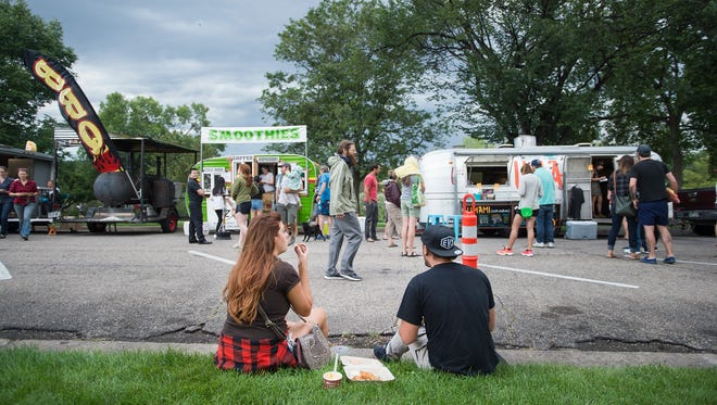 Fort Collins resident Jessica Ream, left, and Cheyenne resident Christopher Sara, right, sit on the curb to enjoy their food, Tuesday, August 15, 2017 during the Food Truck Rally at City Park in Fort Collins, Colo.