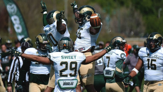 CSU linebacker Josh Watson (55) celebrates with teammates Kevin Nutt Jr. and Justin Sweet after intercepting a pass in the April 22 Green and Gold Spring Game. They represent three of the seven starters back this fall on what coach Mike Bobo and players believe will be a significantly improved defense.