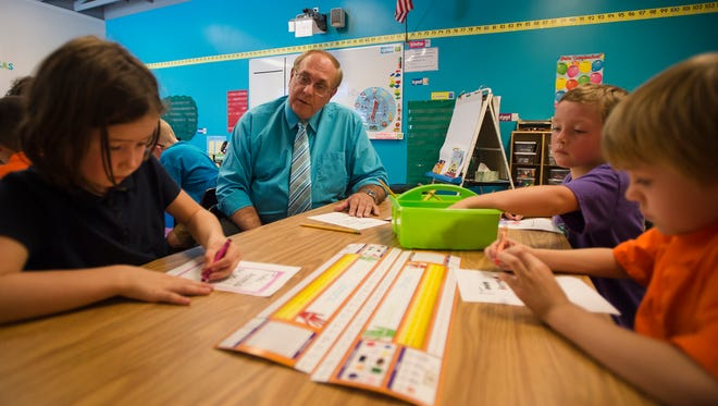 New principal Dave Finley speaks with first graders, from left, Sanora Stuckey, Maddock Smith and Shae Nichols in spanish on the first day of school at Global Village Academy, Wednesday, August 23, 2017, in Fort Collins, Colo.