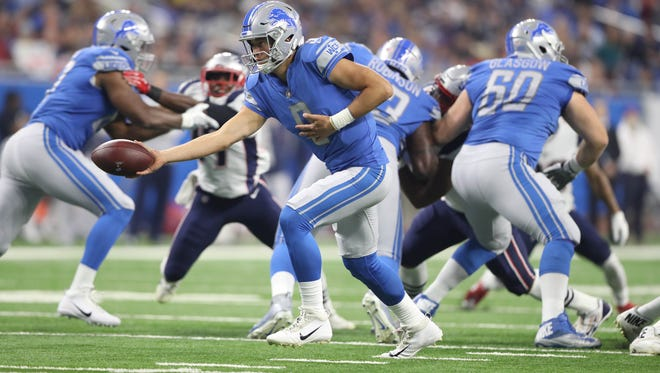 Lions quarterback Matthew Stafford hands off against the Patriots during first half action Friday, August 25, 2017 at Ford Field.
