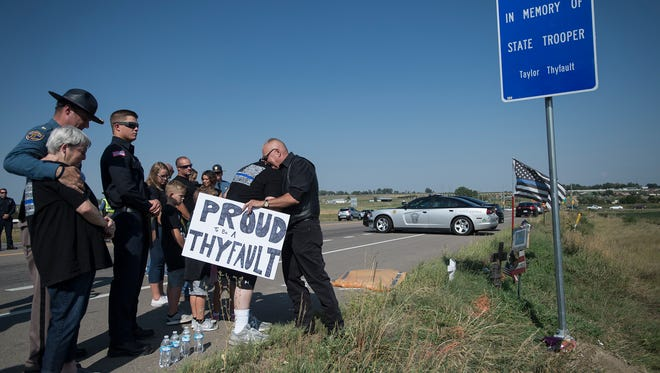 Scenes from a ceremony to unveil a sign to honor slain Colorado State Police Trooper Taylor Thyfault, Monday, August 28, 2017, on State Highway 66, just East of Longmont, Colo.