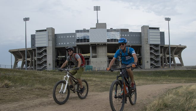 Cyclists make their way North on the Foothills Trail past Hughes Stadium, Tuesday, August 30, 2017, at Maxwell Natural Area in Fort Collins, Colo.