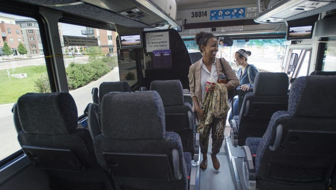 Fort Collins resident Mek D. walks down the aisle of a Bustang bus to commute to Denver at the Downtown Transit Center in First Collins. Bustang has recently announced the addition of weekend service between Denver and Fort Collins.
