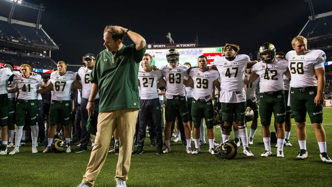 CSU coach Mike Bobo stands in front of his team as they greet the band Friday after being beaten by the University of Colorado in the Rocky Mountain Showdown at Sports Authority Field at Mile High.