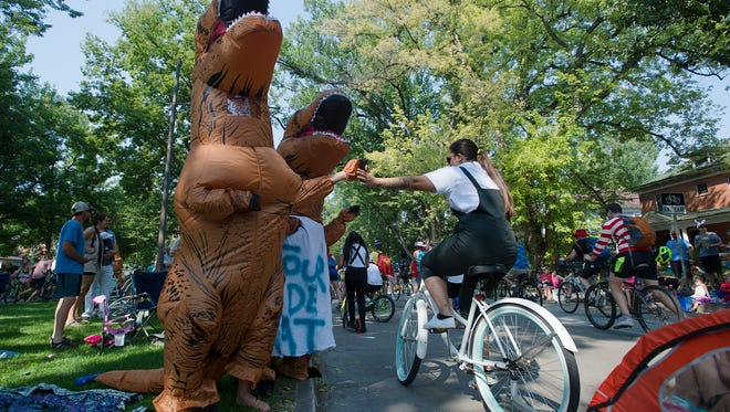 From left, Naomi and Jackie Carlson get high fives from parade participants, Saturday, September 2, 2017, during the Tour de Fat parade in Fort Collins, Colo.