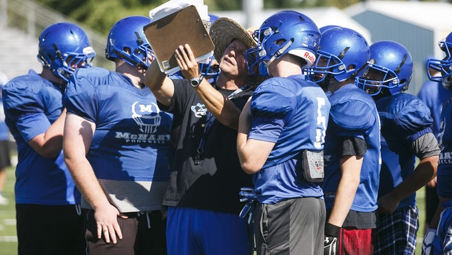 Head Coach Jeff Auvinen huddles with offense line players at a McNary High School football practice on Wednesday, Aug. 16, in Keizer.