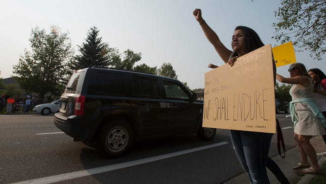 CSU student Carla Lopez clenches her hand in a fist while holding her sign Tuesday, August 5, 2017, during a DACA Solidarity Rally held outside Sen. Cory Gardner's office on South Shields Street in Fort Collins, Colo.