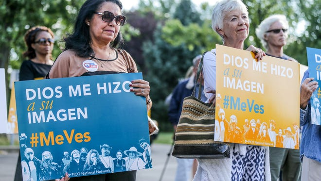 Patricia Cabrera, left, and Mary McDonald, right, had signs during a interfaith press conference and prayer service on DACA held at the St. Gabriel Church in Indianapolis on Tuesday, September 5, 2017.