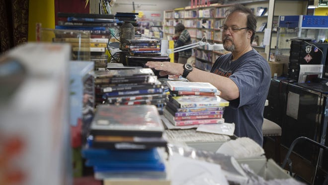Owner Scott Shepherd goes through the drawers of disks as he fills a customer's order, Tuesday, August 8, 2017, during the second day of the total liquidation sale at long-time Fort Collins video rental business The Village Vidiot.