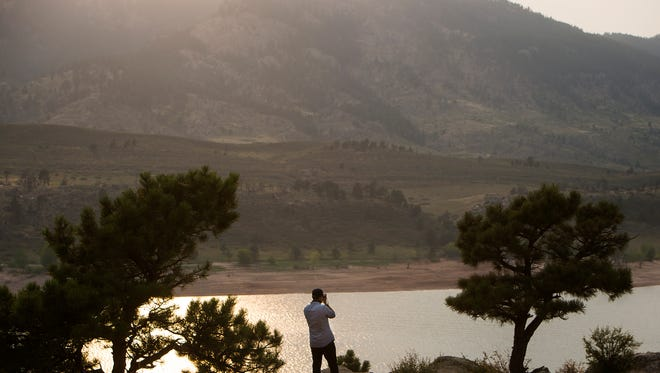 CSU freshman business administration student Alex McVay takes a photo while a smokey haze covers the Rocky Mountains, Wednesday, August 6, 2017, at Horsetooth Reservoir in Fort Collins, Colo.