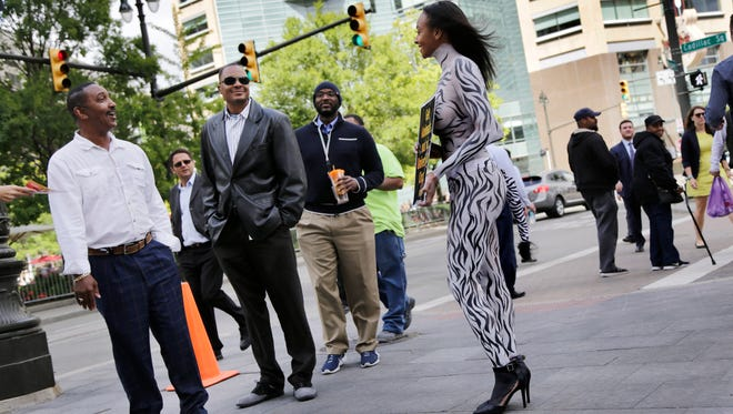 Passerbys Charles Williams, from left Georges Locus, and Kyron Bridges talk with PETA supporter Nikki Ford, 31 of Atlanta who is protesting the use of animals by Universoul Circus downtown Detroit on Thursday, September 7, 2017.