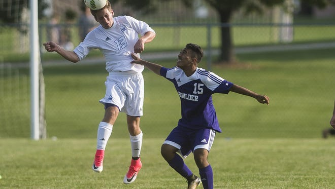 Fort Collins High School senior midfielder Lucas Alessi heads the ball over Boulder High School's Diego Molina on Thursday at Fort Collins High School.