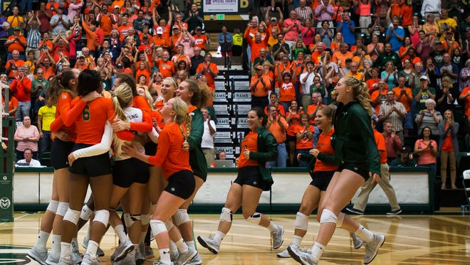 The CSU volleyball team celebrates after beating Michigan, Friday evening, August 8, 2017, at Moby Arena in Fort Collins, Colo.