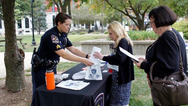 Sgt. Brittney Garrett, left, hands out information about drug addiction to Meredith Daniels, center, whose fiance is in recovery, and Susan Spratt during Kentucky's 3rd Annual Fed Up! International Overdose Awareness Day event held in Jefferson Park in downtown Louisville. Aug. 31, 2017