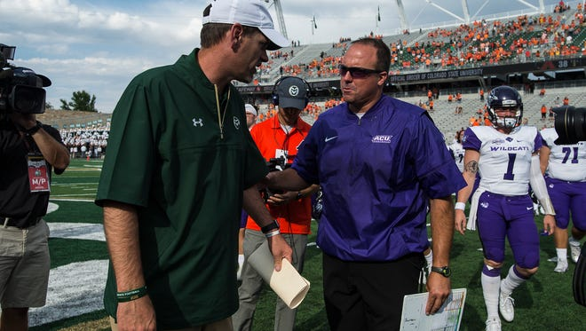 CSU head coach Mike Bobo, left, meets ACU head coach Adam Dorrel after a CSU victory, Saturday, Sept. 9, 2017, at Sonny Lubick Field at Colorado State Stadium in Fort Collins, Colo.