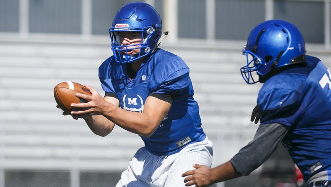 Eric Barker hands off the ball at a McNary High School football practice on Wednesday, Aug. 16, in Keizer.