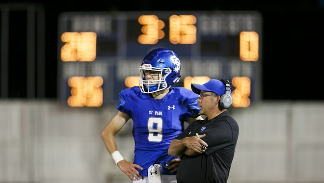 St. Paul head coach Tony Smith and his son and quarterback Holden Smith in a game against Monroe on Friday, Sept. 8, 2017, in St. Paul, Ore. St. Paul won the game 42-12.