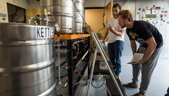 Seniors Kelly Floyd, left, and Kolton Reitsch check the temperature of water heating up for sparging the classes latest batch of beer, Friday, Sept. 8, 2017, during a Brewing Science and Technology class at Colorado State University in Fort Collins, Colo.