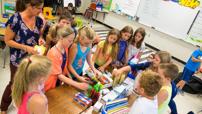 Students in Shelly Kiteley's fourth grade class at Keewahdin Elementary School sort supplies they raised to send to schools in Houston, Texas, Sept. 13.