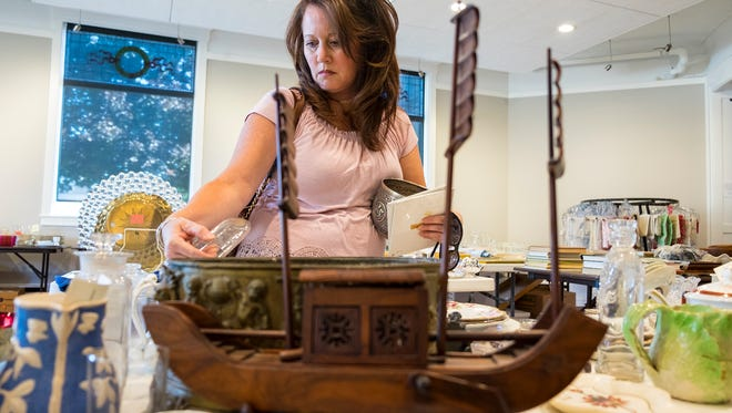 Becky Barno looks over items being auctioned off at the Port Huron Museum Sept. 13. The auction will be held Saturday at the museum.