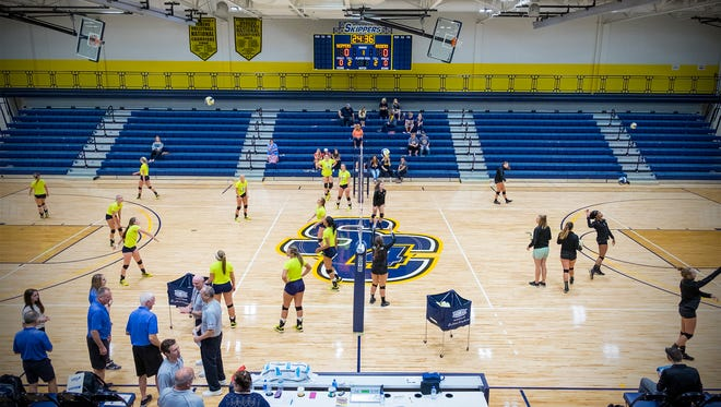 The SC4 Skippers and the Oakland Community College Raiders warm up before the first volleyball game in the completed SC4 field house Sept. 14.