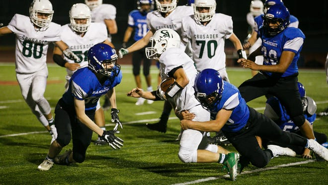 Salem Academy's Jacob Haller (5) is taken down by Blanchet defense in a PacWest Conference game on Friday, Sept. 15, 2017, at McCulloch Stadium in Bush's Pasture Park. Blanchet won the game 22 to 12.