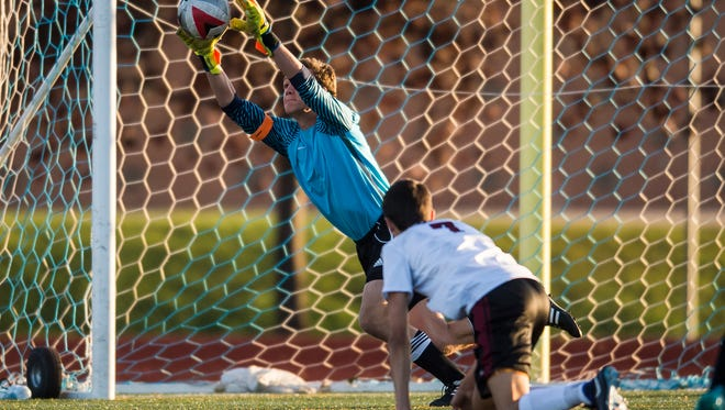 Fossil Ridge High School goalkeeper Logan Wette (1) saves a goal from Rocky Mountain High School freshman Jake Swan (7), Tuesday, Sept. 19, 2017, at Rocky Mountain High School in Fort Collins, Colo.