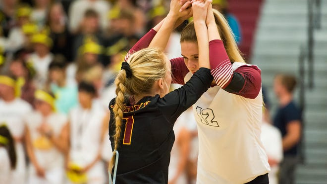 Rocky Mountain High School AnnaMarie Dodson (12) and Annika Larson (1) prepare each other before a game against Fort Collins High School, Tuesday, Sept. 19, 2017, at Rocky Mountain High School in Fort Collins, Colo.