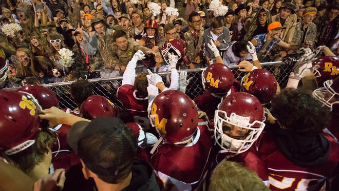 The Rocky Mountain High School football team rushes to the student section after winning a game against Poudre High School on Friday.