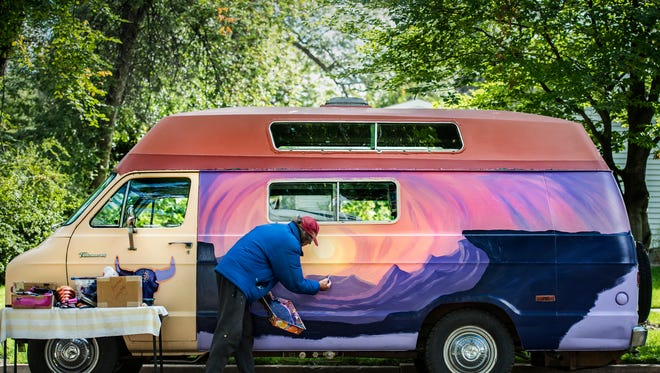 Local artist Werner Schreiber paints a mountainous landscape of a mural on his 1972 Dodge Tradesman 300 van Tuesday afternoon, Sept. 25, 2017, on Mountain Avenue in Fort Collins, Colo. Schreiber, who has been living in Fort Collins for about seven years, has painted seven of the pianos around town, numerous transformers, as well as countless windows and murals in the area.