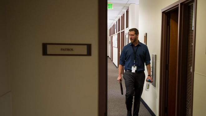 Summitstone Health Partners clinician Jesse Boyd heads out of his workspace, located right alongside Loveland Police officers, at the Loveland Police Department.