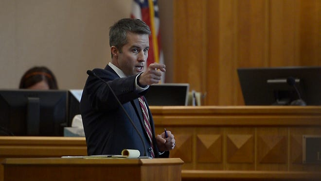 Deputy District Attorney Daniel McDonald reenacts pulling a gun's trigger while addressing the jury, Tuesday, Sept. 26, 2017, during the opening statements of the Tanner Flores trial at the Larimer County Justice Center in Fort Collins, Colo.