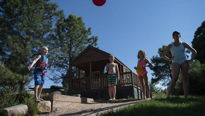 From left, Noah Swedlund, Zach Swedlund, Daynarae Dietrich and their mother Amanda Dietrich play a round of frisbee golf at the camper cabin they rented for the weekend on the west side of the South Bay Campground at Horsetooth Reservoir in August.