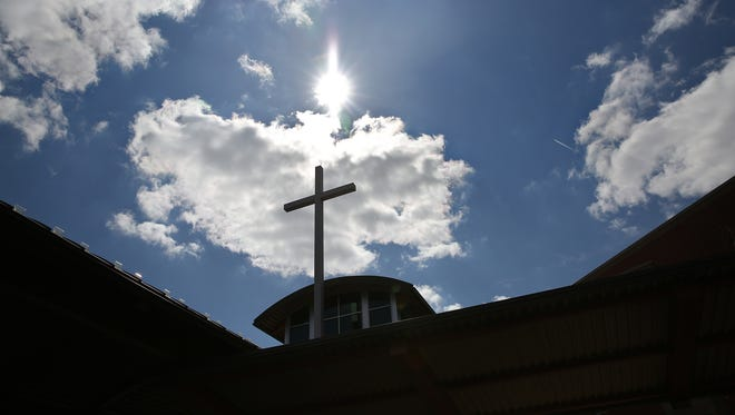 A cross rises towards the sun at Traders Point Christian Church, March 21, 2016.