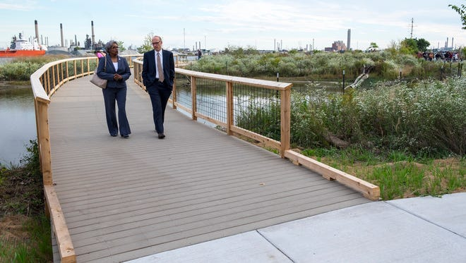 Port Huron Mayor Pro Tem Anita Ashford, left, walks on the new boardwalk at the Wetlands County Park with Greg Stremmers