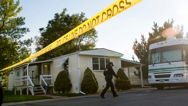 A Fort Collins police officer walks past the police tape blocking off a home near West Wilcox Lane and Highway 287. Investigators have ruled this death a homicide.