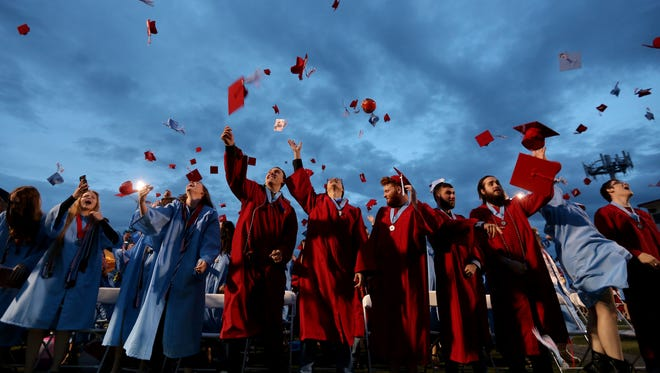 Graduates throw their caps in the air during the South Salem High School commencement at South Salem High School on Friday, June 9, 2017.