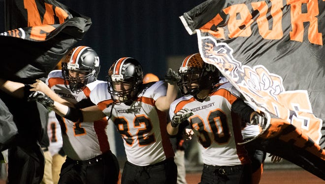 Middlebury break through their banner as they make there way onto the field at the end of halftime during the high school football game between the Middlebury Tigers and the Burlington Seahorses at Buck Hard field on Friday night.