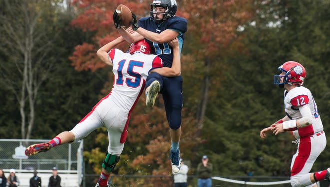 MMU's Harrison Leombruno-Nicholson (11) leaps over Hartford's Riley Kehoe (15) to catch the ball during the high school football game between the Hartford Hurricanes and the Mount Mansfield Cougars at MMU High School on Saturday afternoon October 14, 2017 in Jericho.