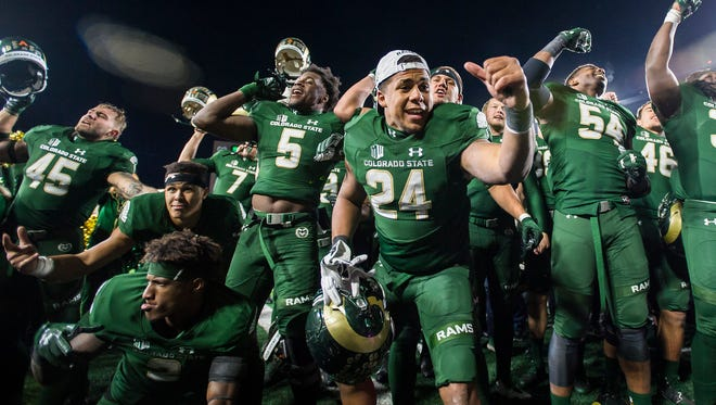 Running back Izzy Matthews (24) and his CSU teammates celebrate while singing the school fight song late Saturday night after beating Nevada 44-42 in their annual homecoming game.