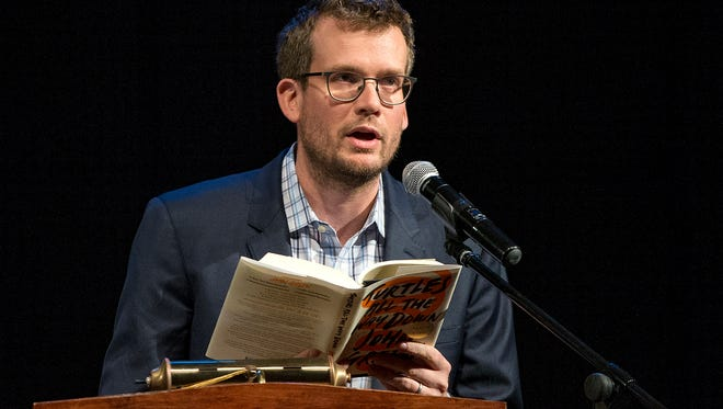 """Author John Green reads an excerpt from """"Turtles All the Way Down,"""" during his appearance at the Pike Performing Arts Center, Indianapolis, Thursday, Oct. 19, 2017. Green read an excerpt from the book and answered audience questions before his brother Hank Green joined the stage to entertain."""
