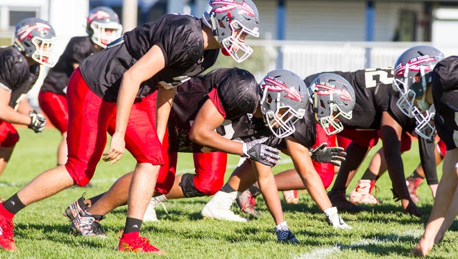 The Port Huron Big Reds run drills at a football practice Oct. 18. The Crosstown Showdown football game against Port Huron Northern will be played Friday.