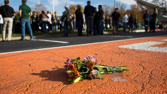 A bouquet of flowers is taped down on the orange stripe on Meridian Avenue, Friday afternoon, Oct. 20, 2017, at a vigil for slain CSU senior Savannah McNealy, on campus in Fort Collins, Colo.