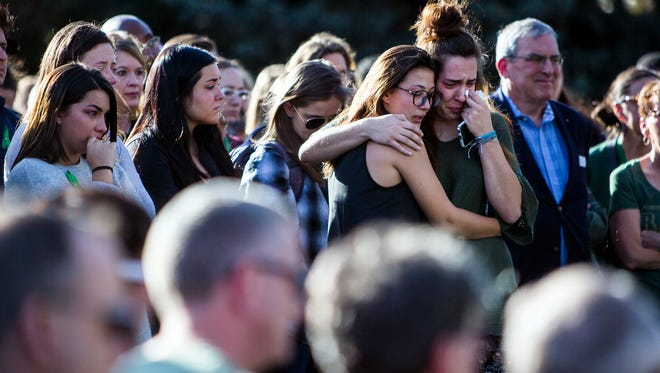Friends of slain Colorado State University senior Savannah McNeal hug each other Friday afternoon, Oct. 20, 2017, at a campus vigil in Fort Collins, Colo.